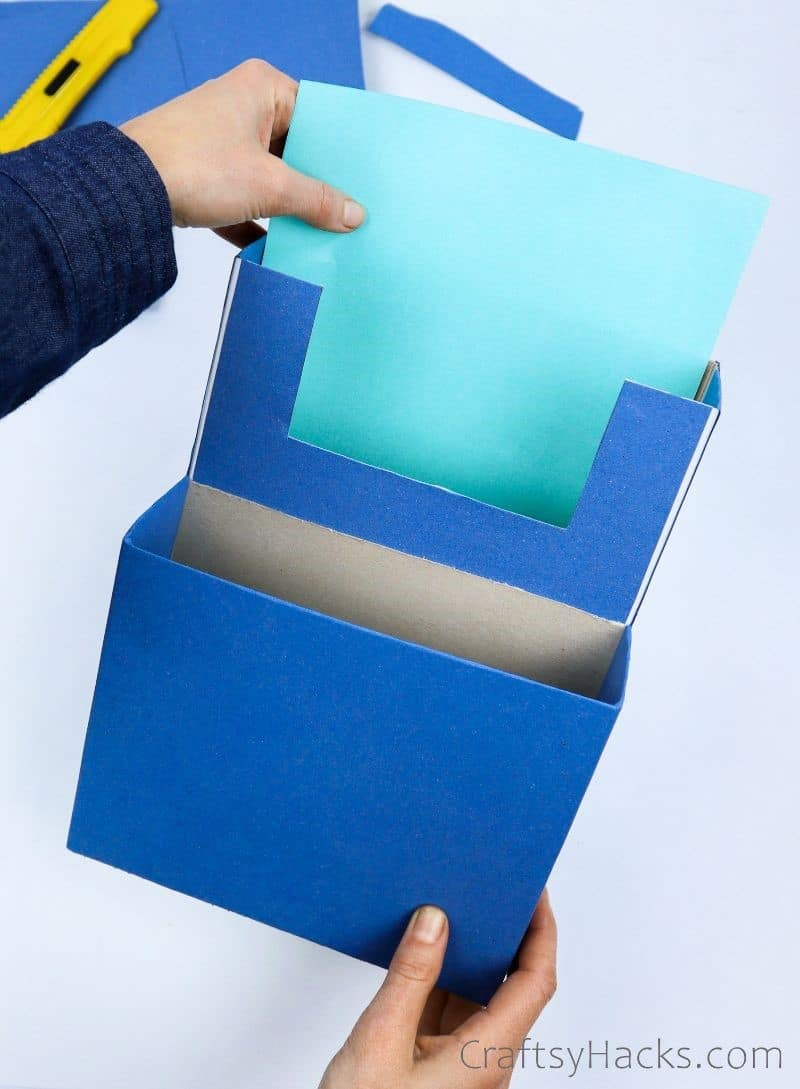 adding teal paper to inside of box
