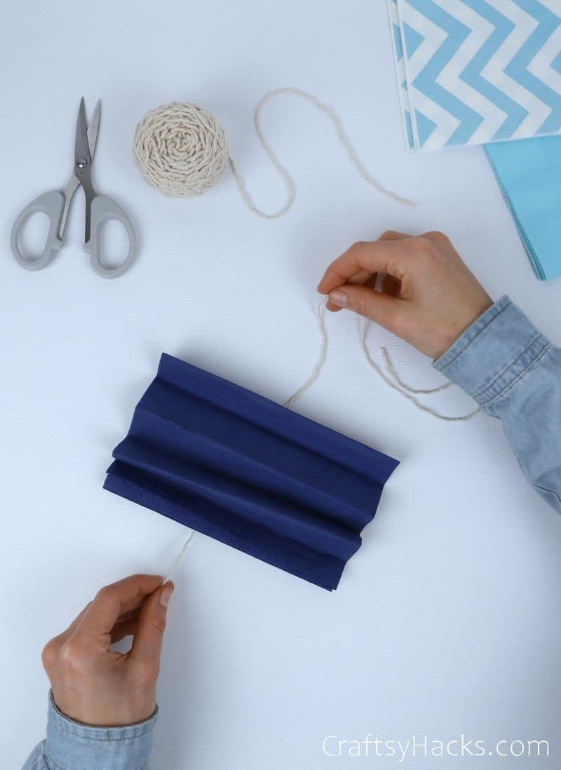 wrapping string around folded tissue paper