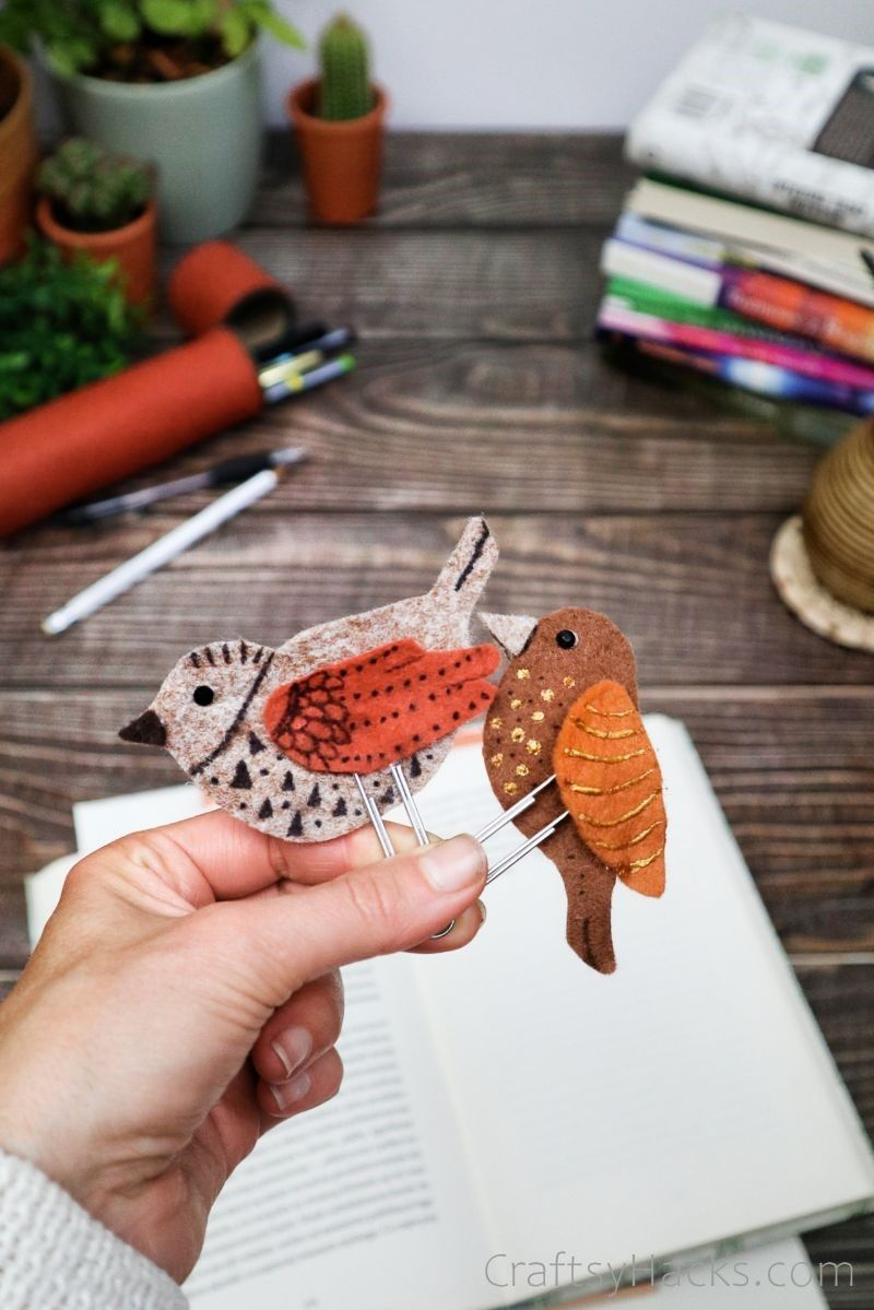 holding two completed bird bookmarks