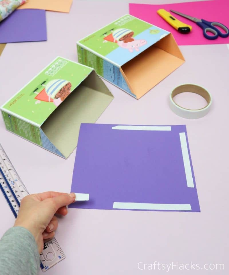 adding adhesive strip to purple paper