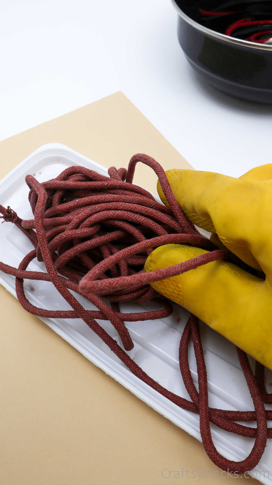 holding red dyed rope with glove