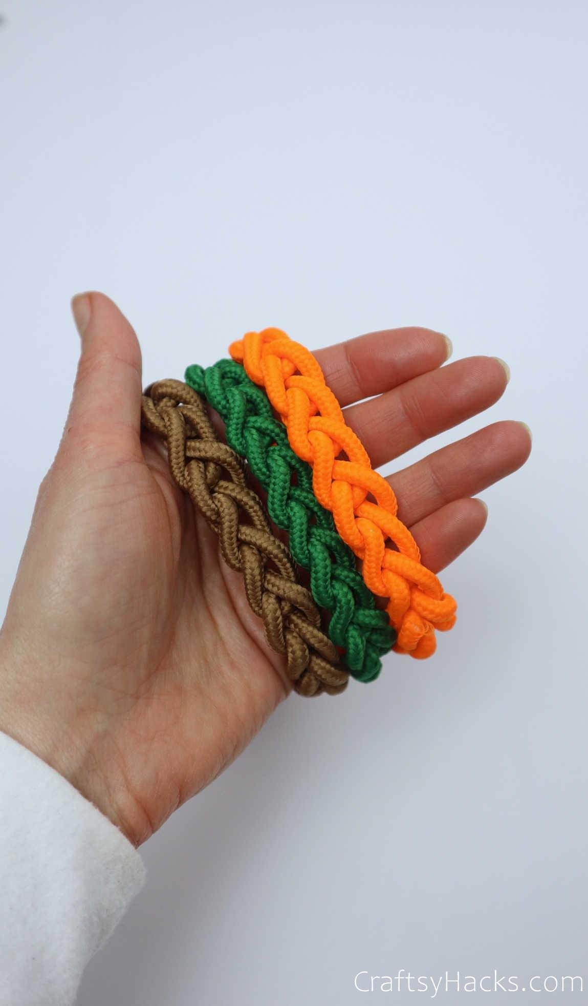 holding brown, green, and orange bracelets