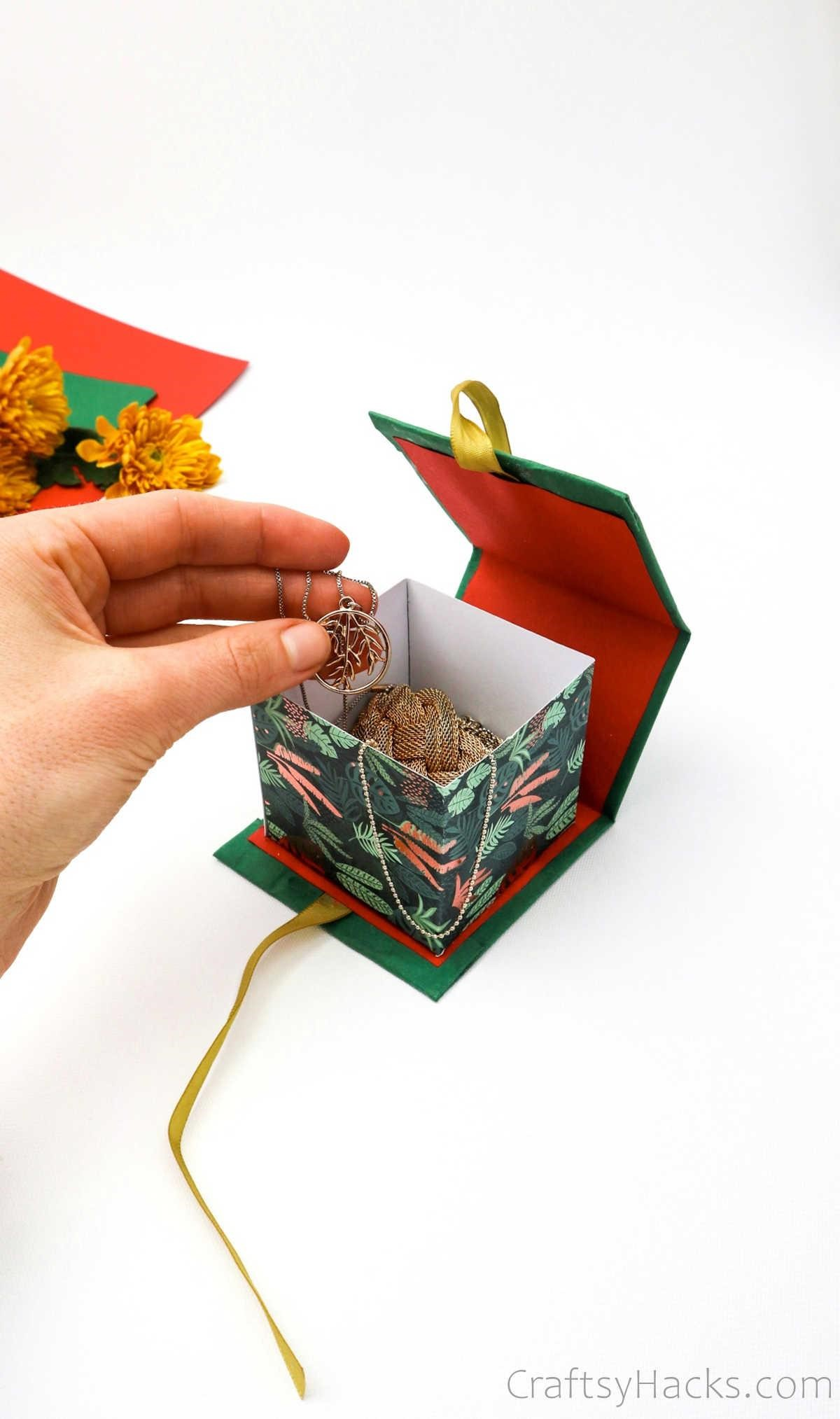 holding necklace above gift box