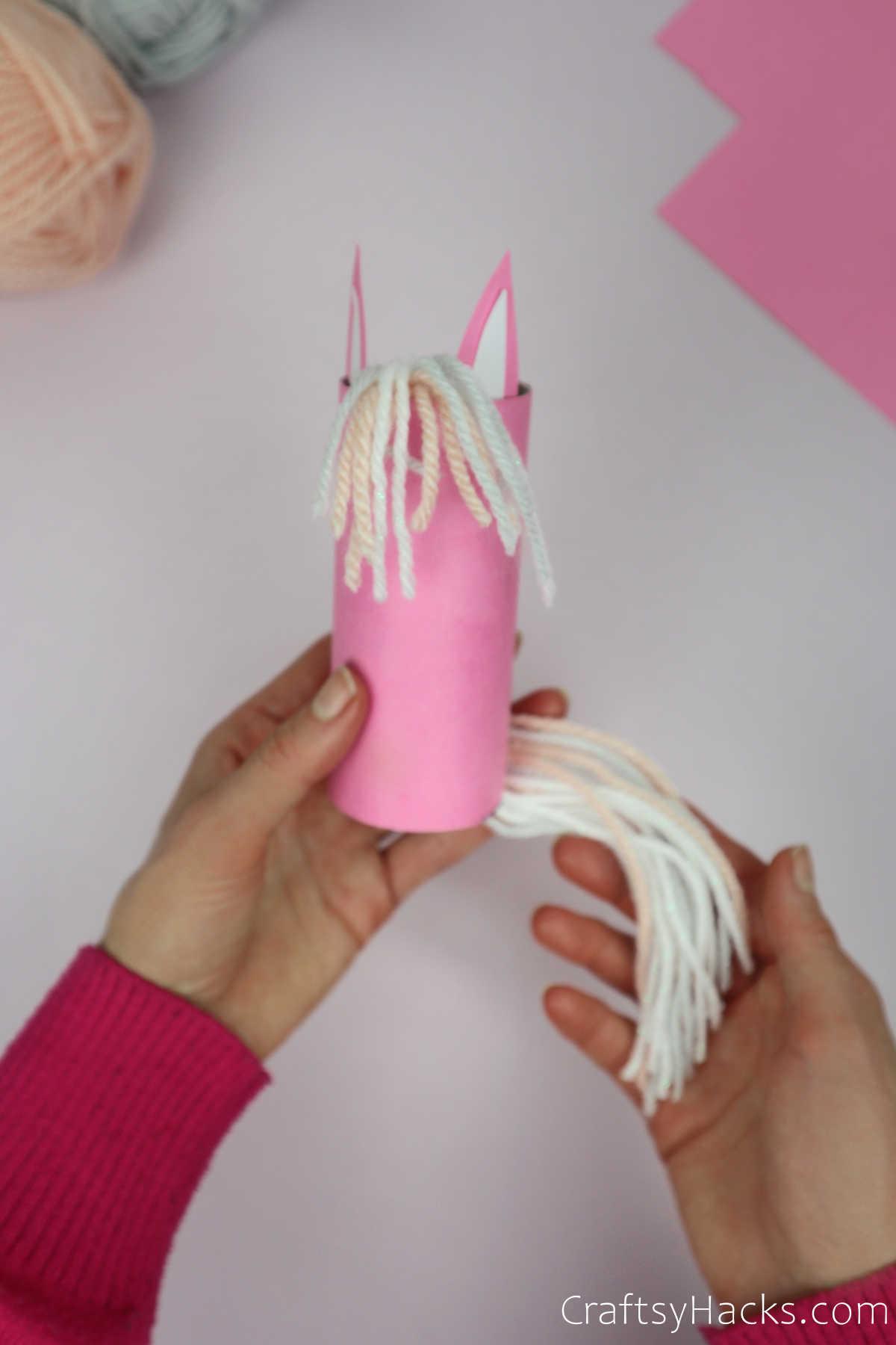 holding unicorn with yarn