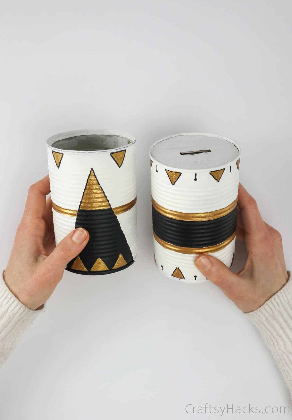 holding two tin cans painted