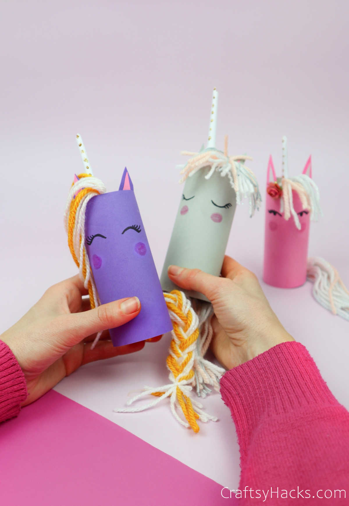 holding two paper roll unicorns