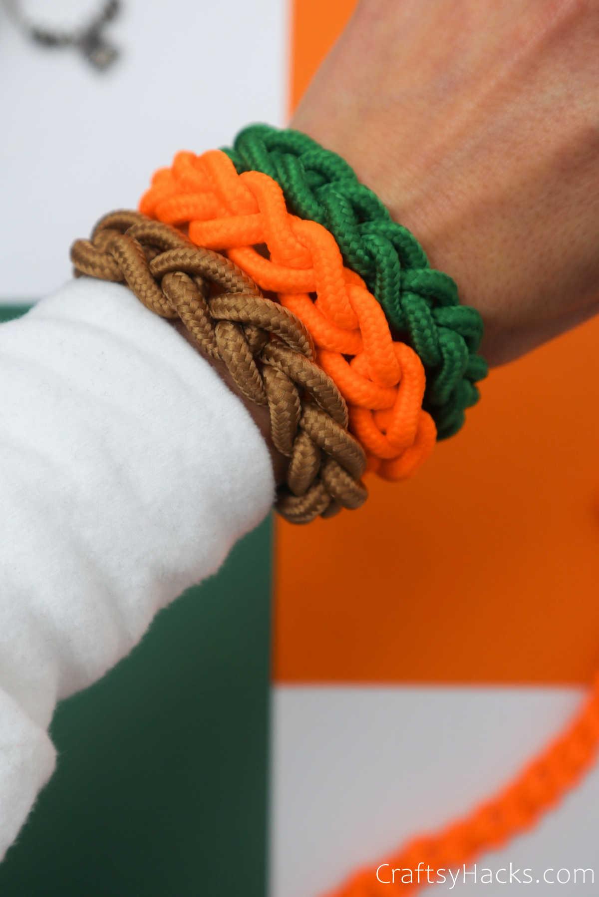 green, orange, and brown DIY bracelets on wrist