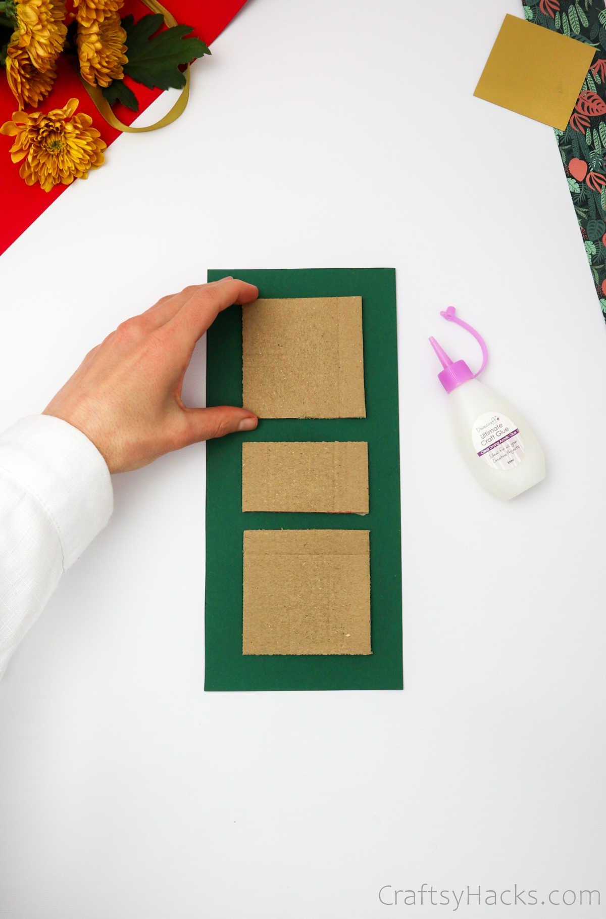 glueing cardboard squares to paper